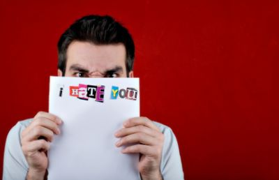 man hiding behind hate letter
